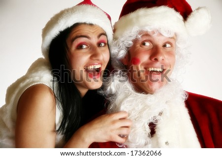 Beautiful young middle eastern woman kissing fake santa. - stock photo
