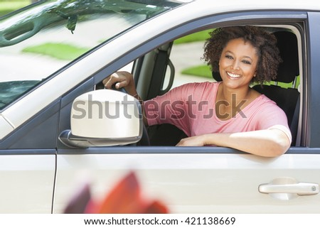 Beautiful young mixed race black African American woman driving a car - stock photo