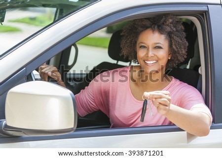 Beautiful young mixed race black African American woman driving a car and holding the key - stock photo