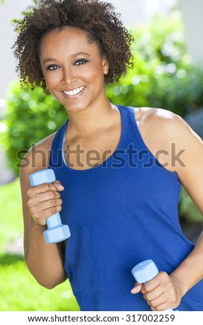 Beautiful young mixed race black African American woman smiling, exercising with weights outside - stock photo