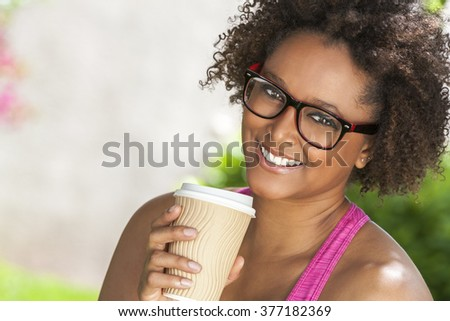 Beautiful young mixed race black African American woman smiling with perfect teeth, wearing glasses and drinking a takeaway cup of coffee outside
