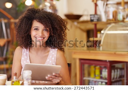 Beautiful young mixed race woman smiling at the camera confidently while using her digital tablet in a coffee shop - stock photo
