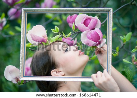 Beautiful young model framing herself with an old picture frame - stock photo