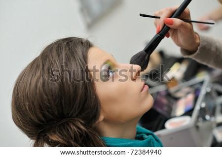 beautiful young model getting fashion make-up - stock photo
