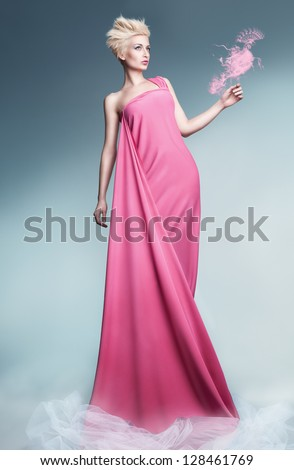 beautiful young model holding a peacock made of smoke wearing long pink dress and posing on blue background - stock photo