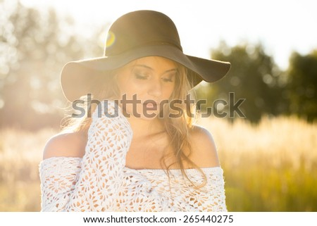 Beautiful young model in field at sunrise - stock photo
