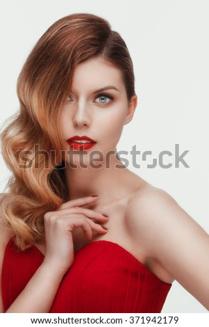 Beautiful young model in red dress  posing in the studio