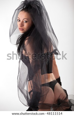 Beautiful young model in veil and black lingerie - stock photo