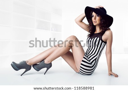 Beautiful young model sitting on floor wearing black hat, black and white stripes dress and grey high heels shoes, legs extended - stock photo