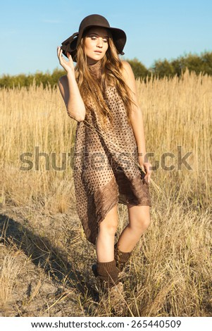 Beautiful young model wandering through meadow at midday - stock photo