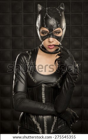 Beautiful young model wearing hand made cat costume in front of black wall. - stock photo