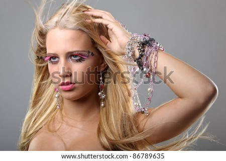 Beautiful young model with blond hair and fake eyelashes in a fashion studio portrait - stock photo