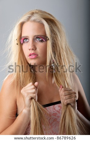 Beautiful young model with blond hair and fake eyelashes in a fashion studio portrait holding the hair - stock photo