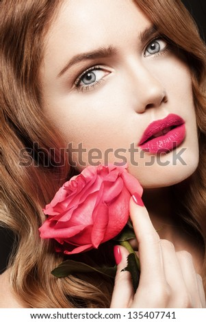 Beautiful young model with bright makeup and manicure and with a rose - stock photo