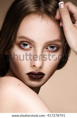 Beautiful young model with dark makeup. Close-up beauty portrait over beige background. Looking at the camera. - stock photo