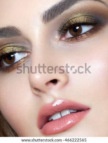 beautiful young model with evening make up, perfect skin. Trendy  golden smoky eyes