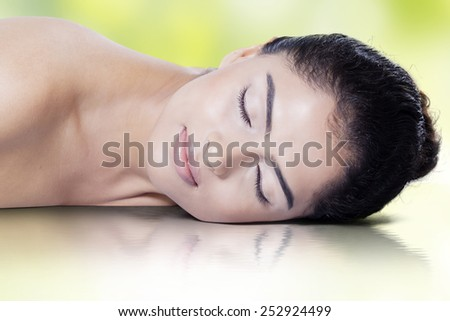 Beautiful young model with fresh skin, relaxing in the studio with water reflection - stock photo