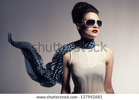 beautiful young model with her scarf flying posing on gray background - stock photo