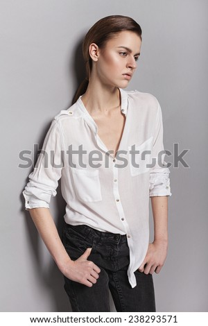 Beautiful young model with  natural make-up on grey background. Androgyne young woman