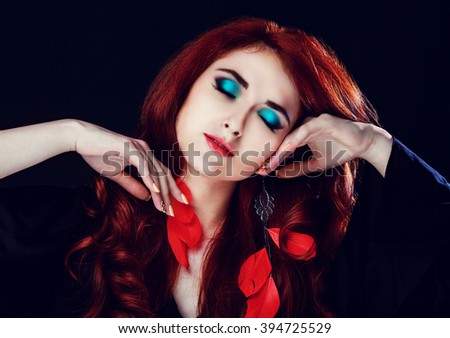 beautiful young model with red hair and bright makeup, against black studio background