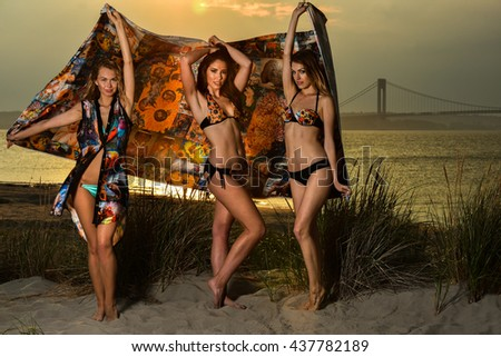 Beautiful young models wearing bikinis posing at sunset beachphotoshoot. - stock photo