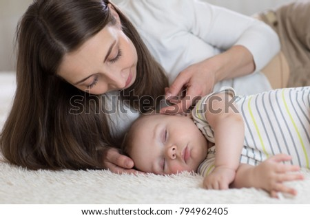 Beautiful young mom and her cute little baby sleeping in bed at home