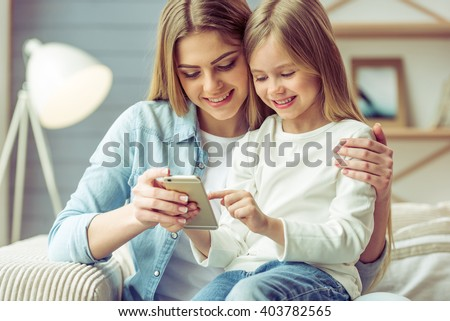 Beautiful young mom and her little daughter are using a smartphone and smiling while sitting on sofa at home - stock photo