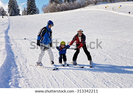 Beautiful young mom, dad and their toddler boy, skiing in the mountains, winter time