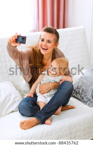 Beautiful young mom making photos with her lovely baby at home