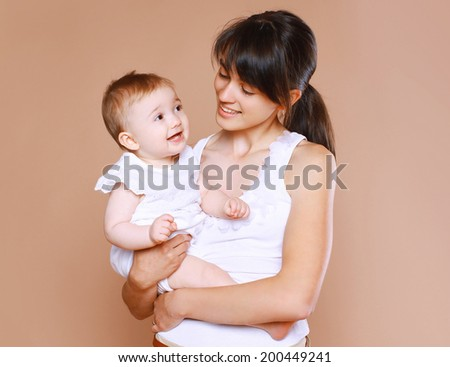 Beautiful young mom with baby - stock photo