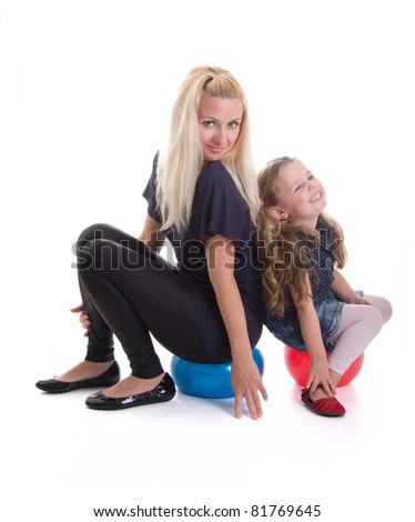 Beautiful young mother and daughter having fun with balls, isolated on white background - stock photo