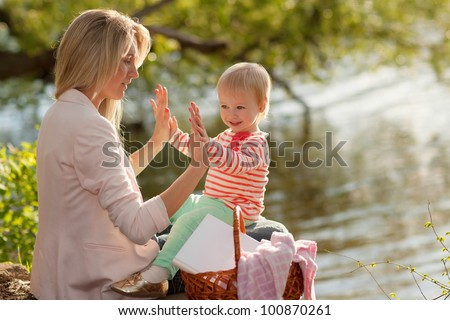 beautiful young mother and daughter playing sitting near the lake - stock photo