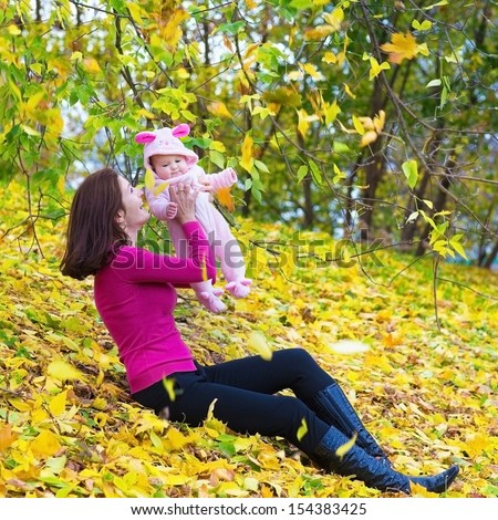Beautiful young mother and her adorable baby daughter playing on yellow autumn leaves in a park on a sunny fall day - stock photo