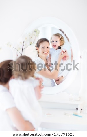 Beautiful young mother and her adorable curly toddler daughter applying make up together in a beautiful white sunny bedroom with an old elegant mirror - stock photo