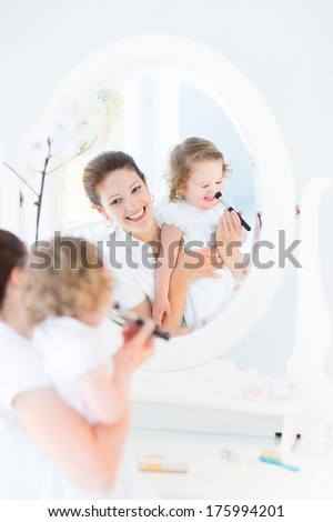 Beautiful young mother and her adorable curly toddler daughter applying make up together in a white sunny bedroom with an old elegant mirror - stock photo