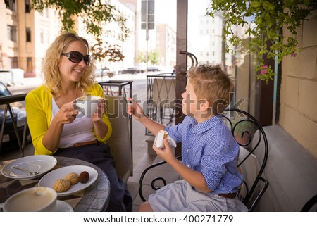 Beautiful young mother and her adorable kid boy sitting outdoors cafe, drinking coffee and tea and talking. Happy two in a summer cafe terrace. Family breakfast outdoor. Mom and child eating. - stock photo