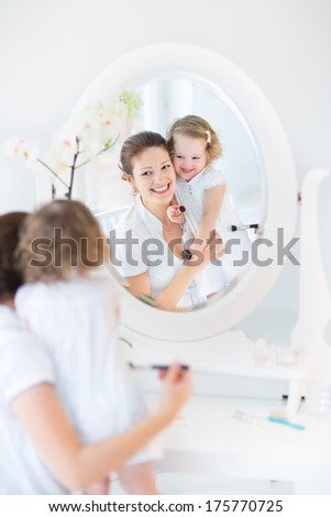 Beautiful young mother and her adorable toddler daughter applying make up together in a beautiful white sunny bedroom with an old elegant mirror - stock photo