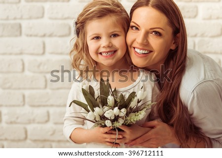Beautiful young mother and her cute daughter are looking at camera and smiling, against white brick wall. Little girl is holding flowers - stock photo
