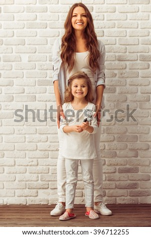 Beautiful young mother and her cute little daughter are looking at camera and smiling while standing against white brick wall - stock photo