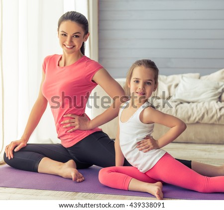 Beautiful young mother and her cute little daughter are looking at camera and smiling while stretching on yoga mat at home
