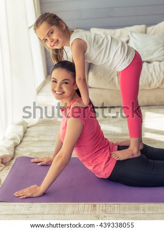 Beautiful young mother and her cute little daughter are looking at camera and smiling while doing yoga at home - stock photo