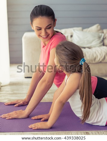 Beautiful young mother and her cute little daughter are looking at each other and smiling while stretching on yoga mat at home - stock photo