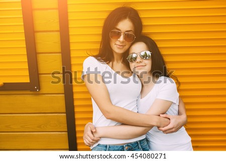 Beautiful young mother and her cute little daughter, looking at camera and smiling, against wall - stock photo