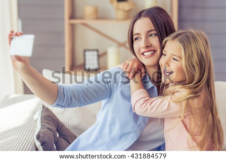 Beautiful young mother and her daughter are making selfie using a phone, hugging and smiling while sitting on the sofa at home - stock photo
