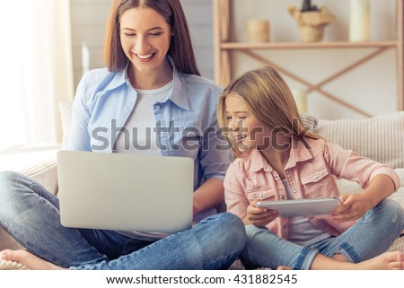Beautiful young mother and her daughter are using gadgets and smiling while sitting in yoga pose on the sofa at home - stock photo
