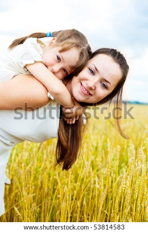 beautiful young mother and her daughter at the wheat field on a sunny day (focus on the child) - stock photo