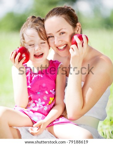 beautiful young mother and her daughter eating apples in the park on a sunny summer day (focus on the woman)