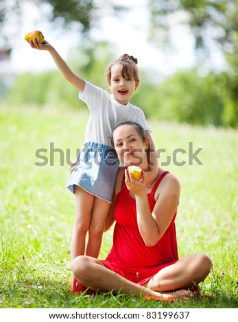beautiful young mother and her daughter eating pears in the park on a sunny summer day (focus on the woman) - stock photo