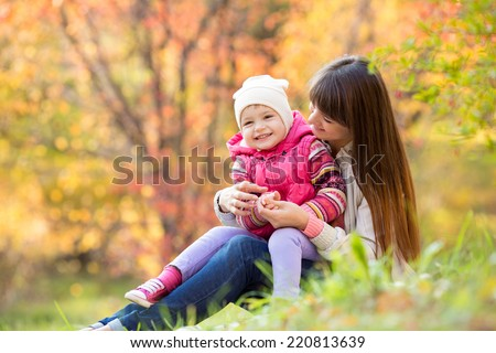 beautiful young mother and her daughter have fun sitting at autumn grass background - stock photo