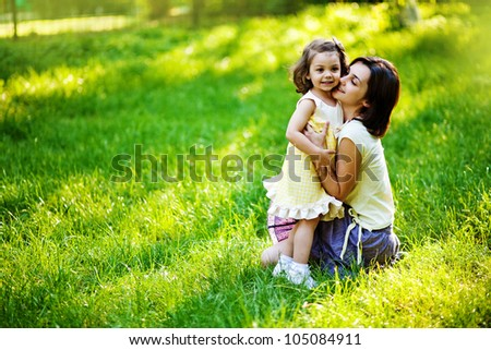 beautiful young mother and her daughter having fun on the green grass - stock photo